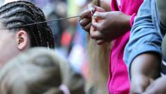 Traditional African braids. Woman braids hair girl on the street. Stock Footage