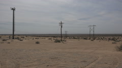California sand and power lines with border fence Stock Footage