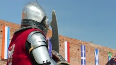 Medieval knight and the walls of the castle. Slow motion Stock Footage