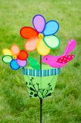 Colorful double pinwheel with bird on green grass Stock Photos