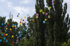 balloons in the sky against trees and the sky, the last call school - stock photo