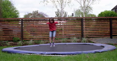 Young girl doing tricks on her trampoline in her garden, in slow motion Stock Footage