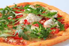Cheese pizza sprinkled with fresh arugula Stock Photos
