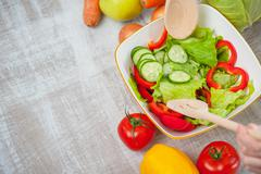 Woman is cooking tasty fresh salad and mingling it Stock Photos
