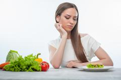 Pretty young woman is choosing between healthy and harmful food Stock Photos