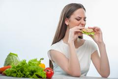 Stock Photo of Beautiful young girl is eating unhealthy food