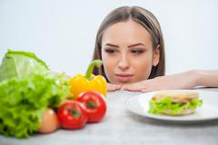 Beautiful young lady chooses between healthy and unhealthy food Stock Photos