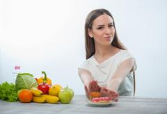 Stock Photo of Beautiful young woman is refusing to eat unhealthy food