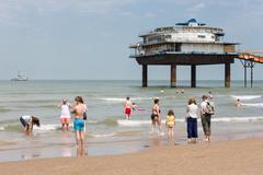 Seaside visitors at Dutch beach near Pier of Scheveningen - stock photo