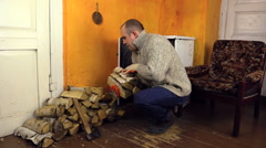 Man with woolly sweater bring wood, leave axe gloves near stove Stock Footage