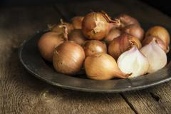 Moody natural lighting vintage retro style image of fresh shallots Stock Photos