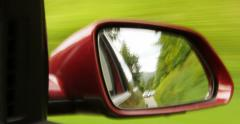 Wining road through the mirror of a car moving fast Stock Footage