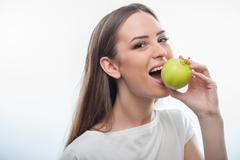 Beautiful healthy woman is eating green fruit - stock photo