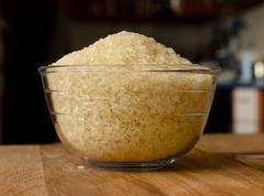 rice grits in a glass bowl on a wooden table - stock photo