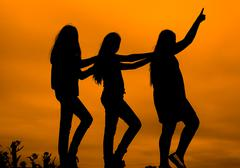 Three girls dancing silhouette at sunset on a background of sky Stock Photos