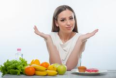 Beautiful young girl is choosing between healthy and unhealthy food Stock Photos