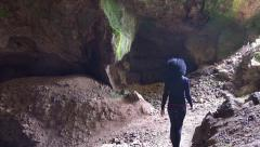 Girl walking through a giant cave. UHD 4K steadycam stock footage Stock Footage