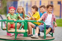 Kids on carousel Stock Photos