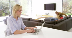 Timelapse of attractive woman working from home on laptop, ignoring her busy Stock Footage
