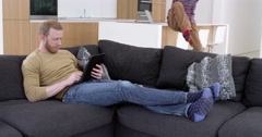 Boy dives onto sofa to look at tablet with dad in contemporary modern home, Stock Footage