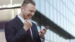 "successful businessman looking at the phone screen says ""yes"" and enjoys success - stock footage"
