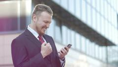 "Successful businessman looking at the phone screen says ""yes"" and enjoys success Stock Footage"