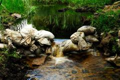 Sandbags create small waterfall Stock Photos
