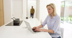 Portrait of attractive couple as woman works from home as partner comes and - stock footage
