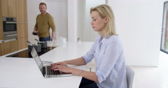 Attractive woman works from home as partner comes and happily chats to her about - stock footage