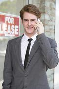 man in front of a store on the phone - stock photo