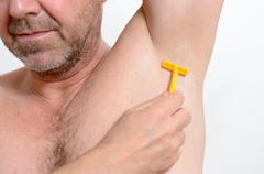 Man shaving under his armpit Stock Photos