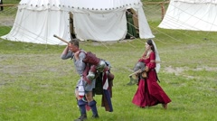 Medieval knight carries his armor. Slow motion. Medieval village in background. Stock Footage