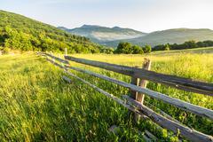 fence on hillside meadow in mountain - stock photo