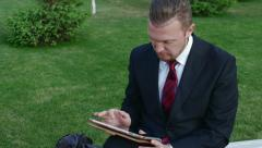 Adult businessman sitting near the office building uses a Tablet PC Stock Footage