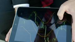 reflection of the face of a businessman in a tablet that looks financial charts - stock footage