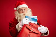 Santa with airline tickets - stock photo