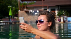 Travel Technology and Vacation - Girl with Mobile Phone in Pool - stock footage