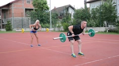 A group of young people in aerobics class doing a dead lift exercise outdoor Stock Footage