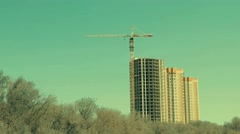 Tower crane on a construction site before buildings and trees - stock footage