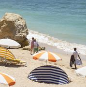Beach seller following holidaymakers on a quiet Algarve beach in Portugal Stock Photos
