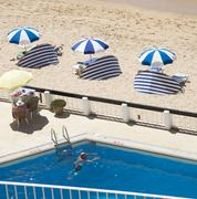 Swimming pool alongside the beach and sea on The Algarve Portugal - stock photo