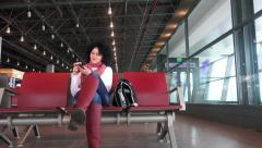 4k Happy teen surfing internet on smartphone sitting relaxed at airport, trai Stock Footage