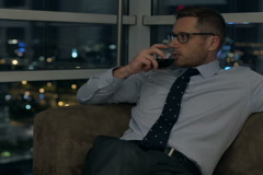 Businessman sitting at night on the sofa and drinking wine Stock Footage