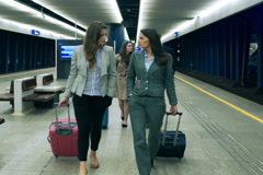 Businesspeople walking with luggage on the station, steadycam shot Stock Footage