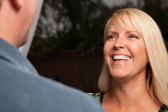 Attractive Blonde Socializing with Man at an Evening Gathering. Stock Photos