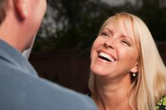 Attractive Blonde Woman Socializing with Man at an Evening Gathering. Stock Photos