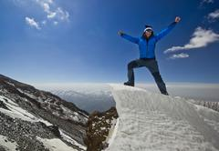 Man standing on a snow cornice in mountain sunrise Stock Photos