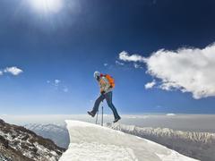 Man jumping on a snow cornice in mountain sunrise Stock Photos
