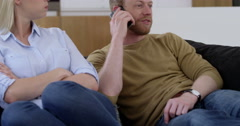 Stock Video Footage of Handsome man chats on cell phone, annoying his girlfriend in contemporary home,