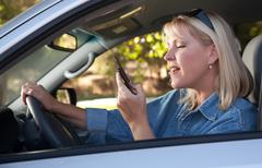 Attractive Blonde Woman Text Messaging on Her Cell Phone While Driving. Kuvituskuvat